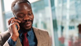 African American businessman talks with someone on his smartphone standing on the street near office center. Business. People, communication, technology stock footage