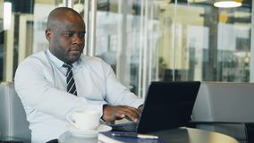 African American businessman thinking, printing and working on his laptop in glassy cafe during lunch break. He is