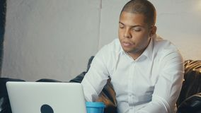 African American businessman uses laptop and drinks coffee while sitting at sofa in modern office looks at monitor. African American handsome businessman uses stock video