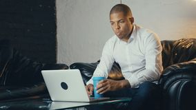 African American businessman uses laptop and drinks coffee while sitting at sofa in modern office looks at monitor. African American handsome businessman uses stock video footage