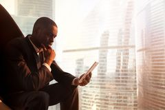 Black CEO reading news online with digital tablet Stock Photography
