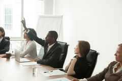 African-american businessman volunteer raising hand at corporate. African businessman in suit raising hand at corporate diverse group meeting, black employee Royalty Free Stock Images