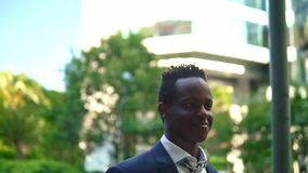 African American businessman wearing blue suit walking. Near office. Business concept stock video footage