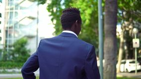 African American businessman wearing blue suit walking. Near office. Business concept stock video