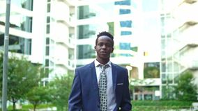 African American businessman wearing blue suit walking. Near office. Business concept stock footage