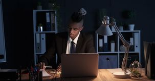 Businessman working late night at office. African american businessman working on laptop and writing on adhesive note at night office stock video