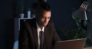 Workaholic businessman working on office laptop at night. African american businessman working late night on office laptop stock video footage