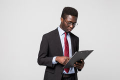 African American businessman writing on a clipboard on grey Stock Photos