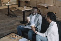 African american businesspeople with coffee to go during meeting. In cafe royalty free stock photos