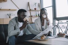 African american businesspeople drinking coffee to go while reading newspaper. In coffee shop stock images