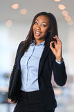 African American Businesswoman. Beautiful African American businesswoman giving the OK sign isolated over white background royalty free stock images