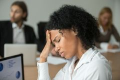African businesswoman feeling unwell suffering from headache at. African american businesswoman feeling unwell suffering from headache migraine touching forehead royalty free stock images