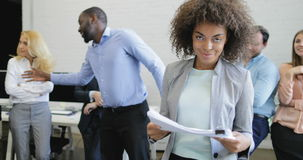 African American businesswoman hold documents smiling over business people group brainstorming meeting in modern open stock video footage