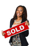African American Businesswoman Holding Sign. Portrait of beautiful African American businesswoman holding sold sign isolated over white background Royalty Free Stock Photography