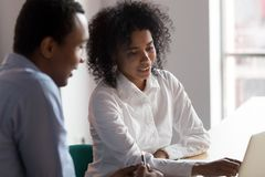 African American businesswoman mentor helping male trainee with project. African American businesswoman mentor helping male trainee with online project or new stock images