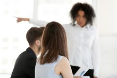 African American businesswoman point at doors asking employees l. Back view of mad African American businesswoman point at doors asking employees leave meeting royalty free stock image