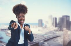 African american businesswoman pointing at camera with skyline o Royalty Free Stock Image
