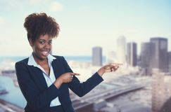 African american businesswoman pointing sideways with skyline of Royalty Free Stock Photography
