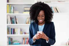 African american businesswoman sending message with mobile phone
