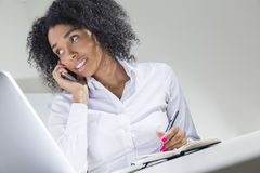 African American businesswoman talking on her phone and writing. Portrait of African American woman talking on her phone, writing stuff down and looking sideways Royalty Free Stock Photo