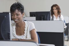 African American Businesswoman Working On Computer. Smiling African American businesswoman working on computer with colleague in background stock photo