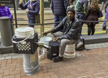 African-American busker playing a makeshift drum kit stock image