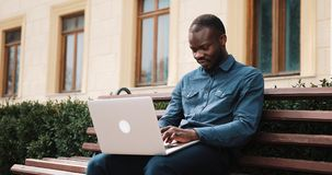 African American bussinesman sits on the bench and works on his laptop.  stock footage