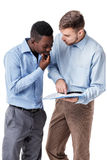 African-American and Caucasian businessman looking at documents Stock Photo