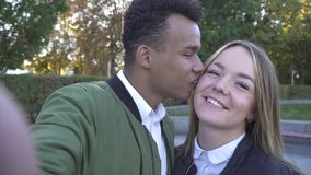 African American and Caucasian couple in love. Beautiful smiling interracial couple in the park. African American guy with his Caucasian girlfriend. Air kiss stock footage
