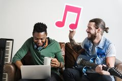 African American and Caucasian male in a songwriting process holding musical note Royalty Free Stock Photography