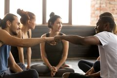 African american and caucasian men fist bumping at group trainin. Smiling sporty fit african american and caucasian men fist bumping at group training meeting in Stock Images