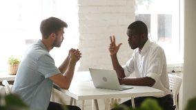 African american and caucasian businessmen negotiating handshaking over office desk stock footage