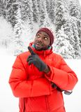African American Cheerful black man in ski suit in snowy winter outdoors Stock Photography