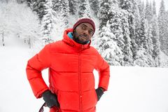 African American Cheerful black man in ski suit in snowy winter outdoors Royalty Free Stock Photos