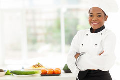 African american chef. Attractive african american female chef with arms folded in restaurant kitchen Royalty Free Stock Photo