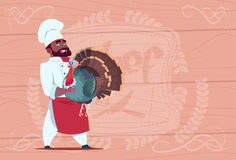 African American Chef Cook Hold Turkey Smiling Cartoon Restaurant Chief In White Uniform Over Wooden Textured Background Royalty Free Stock Image