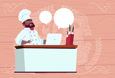 African American Chef Cook Working At Laptop Computer Cartoon Restaurant Chief In White Uniform Sit At Desk Over Wooden Stock Image