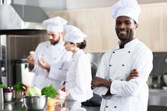 African american chef standing with folded arms in front of his colleagues stock photo