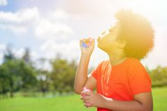 African American child  blowing bubbles in the park in summer Stock Photos
