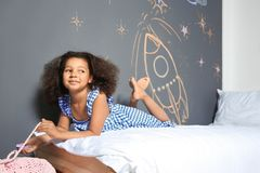 African-American child lying on bed near chalk drawing. Of rocket stock photos