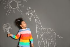 African-American child playing with chalk drawing of giraffe and flowers on grey. Background royalty free stock photo