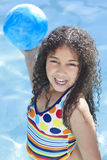 African American Child Playing In Swimming Pool. A cute happy young interracial African American girl child smiling and playing with a ball in a swimming pool Stock Image