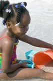 African American child plays at the beach Stock Images
