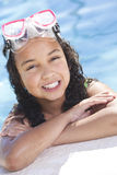 African American Child In Swimming Pool. A cute happy young interracial African American girl child relaxing on the side of a swimming pool smiling & wearing Stock Photography