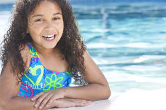 African American Child In Swimming Pool. A cute happy young interracial African American girl child relaxing on the side of a swimming pool smiling Royalty Free Stock Photo