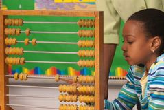 African-American child using a abacus. A student solving  a math assignment using an abacus Stock Photo