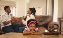 African American children leaning on table while parents arguing on the sofa. Portrait of sad African American children leaning on table while parents arguing on royalty free stock photography