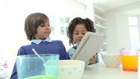 African American Children Use Digital Tablet Over Breakfast. Two children sitting at kitchen counter eating breakfast and using digital tablet.Shot on Canon 5d stock footage