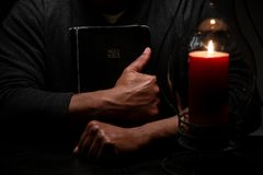 African American Christian Man Embraces the Holy Scriptues, the Bible. African American Christian Man Embraces the Holy Scriptures, the Bible lit by Candle Light royalty free stock image