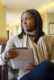 African-American Coed with Digital Tablet. African-american coed sits in student lounge with a digital tablet stock photography